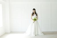 ウェディングドレス姿でブーケを持ち立っている若い女性