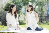 緑のある庭で会話する女性2人