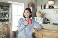 キッチンでカップを持つ20代女性