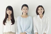 仲良く並んで微笑む20代女性3人