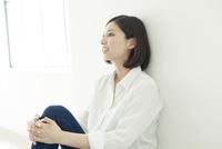 膝を抱えて座る20代女性
