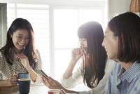 スマホを使う20代女性3人