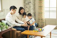 スマホを見る仲良し家族 10161016760| 写真素材・ストックフォト・画像・イラスト素材|アマナイメージズ