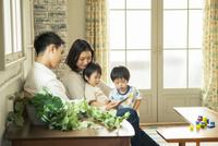 スマホを見る仲良し家族 10161016762| 写真素材・ストックフォト・画像・イラスト素材|アマナイメージズ