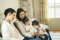 スマホを見る仲良し家族 10161016763| 写真素材・ストックフォト・画像・イラスト素材|アマナイメージズ