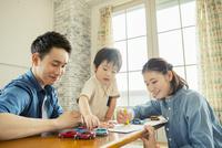 リビングで遊ぶ家族三人 10161016861| 写真素材・ストックフォト・画像・イラスト素材|アマナイメージズ