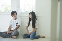 床に座って会話をする20代男女