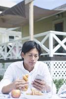 屋外で食事をする20代男性
