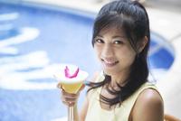 プールでカクテルを飲む女性