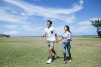 草原でデートする20代男女