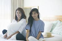 ベッドの上にいる20代女性2人