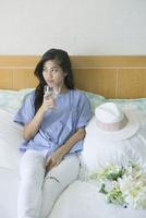ベッドでワイングラスを持つ20代女性