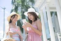 街でスマホ検索をする20代女性2人