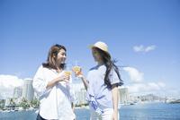 海辺で乾杯する20代女性2人