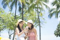 リゾートでスマホ検索をする20代女性2人