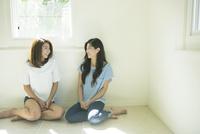 床に座り会話する20代女性