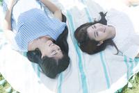 仰向けに寝転ぶ20代女性2人
