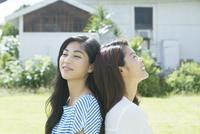 芝生の庭でくつろぐ20代女性2人