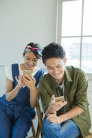 スマホを使う夫婦 10161017522| 写真素材・ストックフォト・画像・イラスト素材|アマナイメージズ