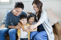 ソファーで写真を撮る家族4人 10161017567| 写真素材・ストックフォト・画像・イラスト素材|アマナイメージズ