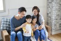 ソファーで写真を撮る家族4人 10161017568| 写真素材・ストックフォト・画像・イラスト素材|アマナイメージズ