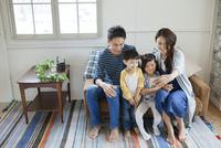 ソファーで写真を撮る家族4人 10161017569| 写真素材・ストックフォト・画像・イラスト素材|アマナイメージズ