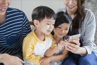 ソファーで写真を撮る家族4人 10161017572| 写真素材・ストックフォト・画像・イラスト素材|アマナイメージズ