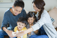 ソファーで写真を撮る家族4人 10161017573| 写真素材・ストックフォト・画像・イラスト素材|アマナイメージズ