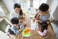 テーブルで遊ぶ家族4人 10161017585| 写真素材・ストックフォト・画像・イラスト素材|アマナイメージズ