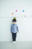 白い壁の前に立つ男の子