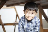 机の下に隠れる男の子
