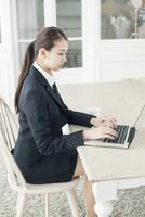 部屋でパソコンを使うスーツ姿の20代女性