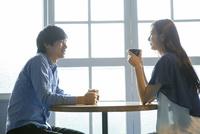 カフェでコーヒーを飲む20代男女