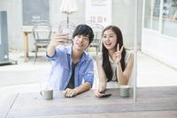 カフェでスマホを使う20代男女