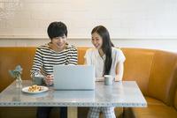 カフェでPCを使う20代男女