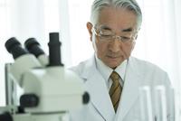 白衣を着た70代男性と顕微鏡