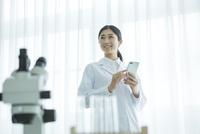 スマホを使う白衣を着た30代女性