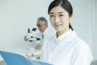 白衣を着た30代女性と顕微鏡を覗く男性 10161018185| 写真素材・ストックフォト・画像・イラスト素材|アマナイメージズ
