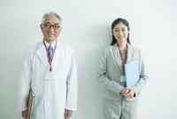 白衣を着た70代男性と会社員女性