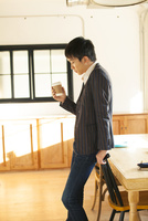 部屋でホットドリンクを手に持つ20代男性 10161018467| 写真素材・ストックフォト・画像・イラスト素材|アマナイメージズ