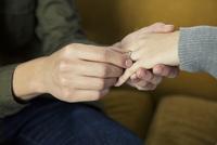 彼女に指輪をはめる20代男性手元