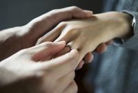 彼女に指輪をはめる20代男性
