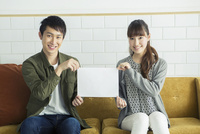 ソファに座り紙を持つ笑顔のカップル