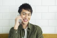 部屋で電話をする20代男性 10161018516| 写真素材・ストックフォト・画像・イラスト素材|アマナイメージズ