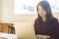 部屋でパソコンを操作する20代女性