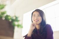 部屋で勉強をする笑顔の20代女性