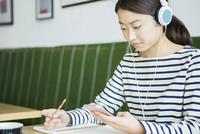 カフェで音楽を聴く20代女性