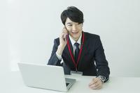 オフィスで通話をするスーツ姿の20代男性 10161018711| 写真素材・ストックフォト・画像・イラスト素材|アマナイメージズ