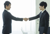 握手をするスーツ姿の20代男性2人