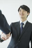 握手をするスーツ姿の20代男性